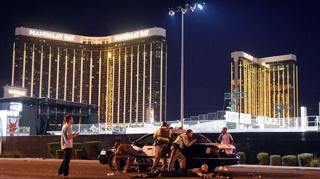 Las Vegas police take cover near the Mandalay Bay Hotel where a gunman was firing at people below. Source: Getty