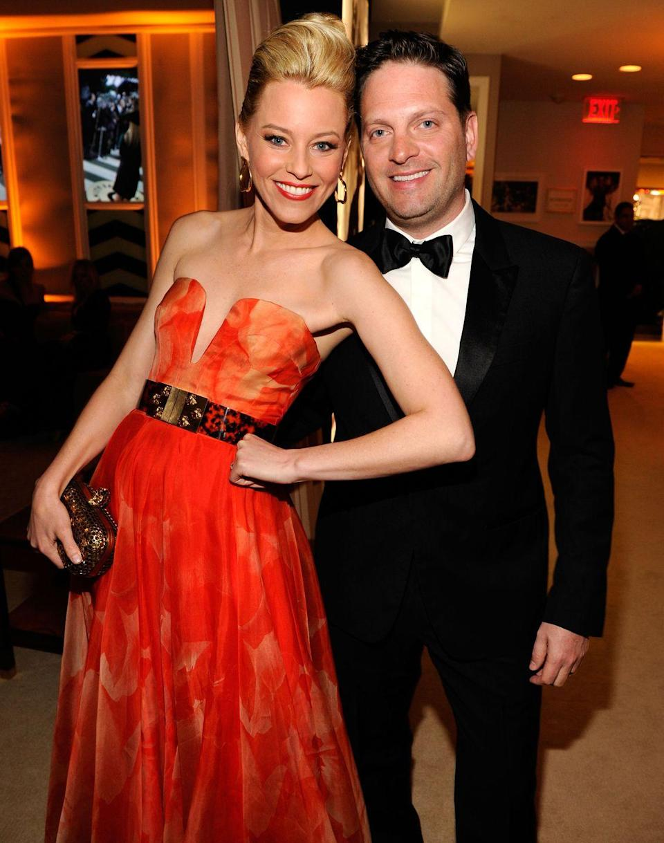 """<p>Elizabeth Banks met her investment banker husband, Max Handelman, at their alma mater: University of Pennsylvania. The pair, <a href=""""https://www.huffpost.com/entry/elizabeth-banks-husband_l_5dd8212ae4b0913e6f6bf461"""" data-ylk=""""slk:who've been together for 27 years"""" class=""""link rapid-noclick-resp"""">who've been together for 27 years</a>, are now partners in a production company, Brownstone Productions, and have two sons together. </p>"""