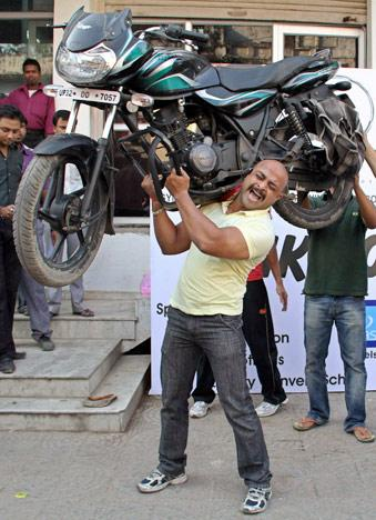 Rahul Tiwari, 28-year-old health trainer lifts a motorcycle weighing 120 kilograms (265 pounds) during a fitness programe in the northern Indian city of Lucknow October 17, 2011. Tiwari lifted the motorcycle after being inspired by Bollywood actor John Abraham who lifted a motorcycle weighing 115 kilograms last month, Tiwari said on Monday. REUTERS/Pawan Kumar
