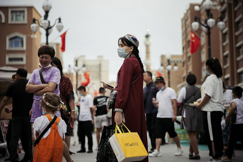 People with face masks walk on the street of Xinjiang.