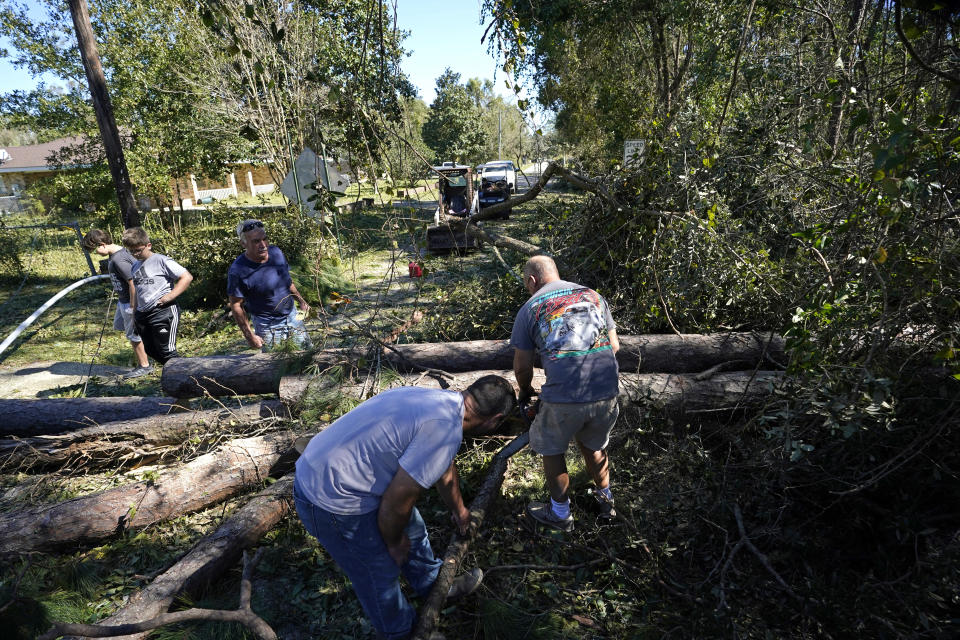 Residents use chain saws to clear fallen trees in the aftermath of Hurricane Zeta in Waveland, Miss., Thursday, Oct. 29, 2020. (AP Photo/Gerald Herbert)