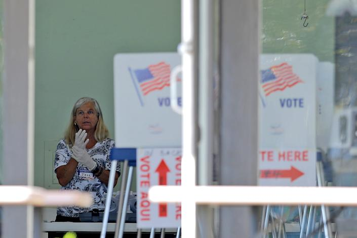 A polling place worker adjusts gloves as she tends to a reception table during the Florida primary election at the First United Methodist Church, Tuesday, March 17, 2020, in Jupiter, Fla. As Florida officials try to contain the spread of the novel coronavirus, the state's voters headed to the polls to cast ballots in the Democratic presidential primary.
