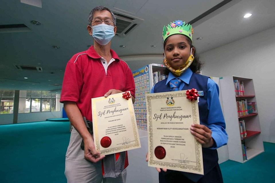 V. Kiranyaah(right) and Phuan Im Wah receiving their awards by Tun Razak Library for their reading habits.