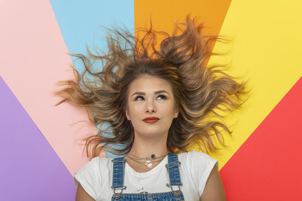 Young woman lying on multicolor Background.Studio Shot