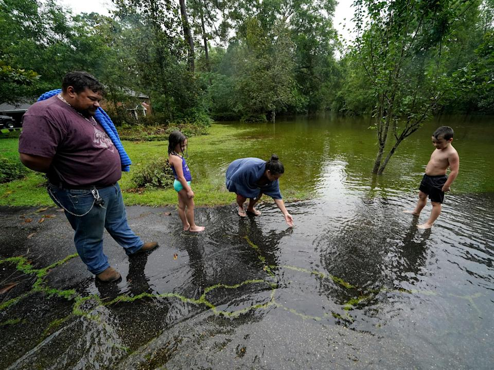 Cal Kingsmill, Jr, and his wife Jessie Kingsmill, point out crickets to their children Marina, 8, and Raylan, 8, in the receding floodwater in front of their home, after Tropical Storm Claudette passed through (AP)