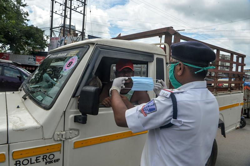 A police personnel (R) distributes a facemask to a motorist near a contained area after some residents allegedly tested positive for the COVID-19 coronavirus in Siliguri on June 17, 2020. (Photo by Diptendu DUTTA / AFP) (Photo by DIPTENDU DUTTA/AFP via Getty Images)