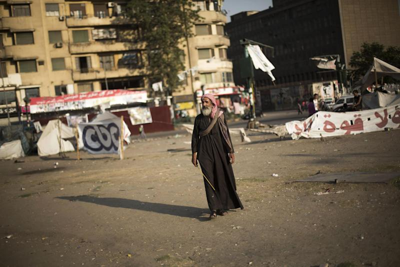 An Egyptian man walks through Tahrir Square where a few protesters have built their camp protesting against the release of Egypt's ousted President Hosni Mubarak in Cairo, Egypt, Saturday, Aug. 24, 2013. (AP Photo/Manu Brabo)