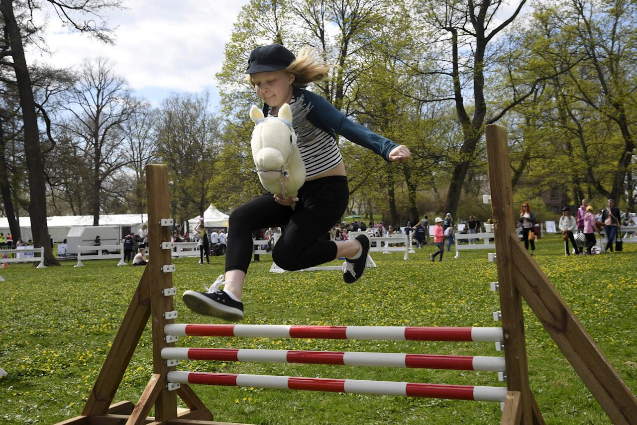 Girl jumps over a hobby horsing fence during a Finland 100 equestrian event in Helsinki, Finland May 20, 2017. Markku Ulander/Lehtikuva/via REUTERS ATTENTION EDITORS - THIS IMAGE WAS PROVIDED BY A THIRD PARTY. FOR EDITORIAL USE ONLY. NO THIRD PARTY SALES. NOT FOR USE BY REUTERS THIRD PARTY DISTRIBUTORS. FINLAND OUT. NO COMMERCIAL OR EDITORIAL SALES IN FINLAND.?
