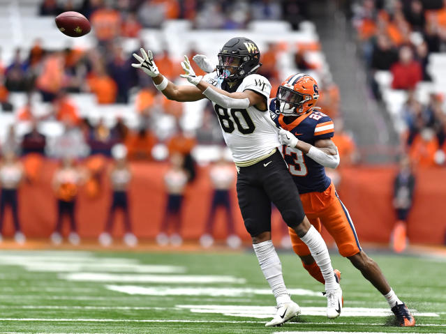 Wake Forest wide receiver Waydale Jones, left, makes a catch while defended by Syracuse defensive back Ifeatu Melifonwu during the first half of an NCAA college football game in Syracuse, N.Y., Saturday, Nov. 30, 2019. (AP Photo/Adrian Kraus)