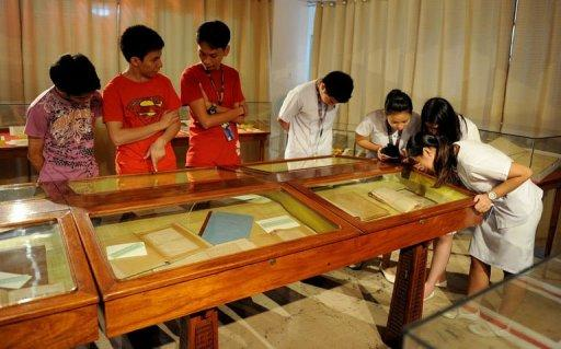 "Students view the restored hand-written novels, the original editions, of national hero Jose Rizal's books ""Noli Me Tangere"" (Touch Me Not) and ""El Filibusterismo"" (Reign of Greed) at the National Library in Manila in June 2011. Tropical conditions and the library's threadbare budget are big obstacles to saving them for future generations"