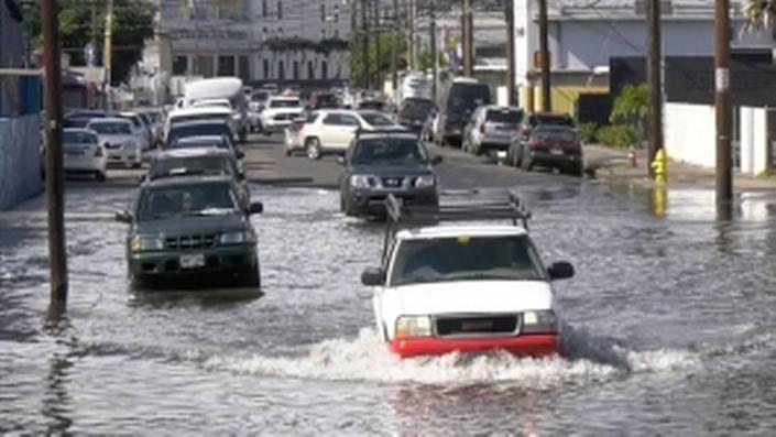 Vehicles drive through a flooded road in Honolulu.