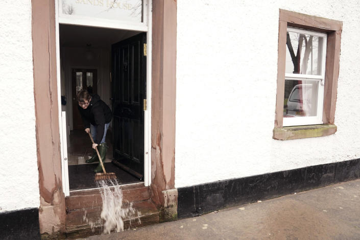 A resident sweeps floodwater from a property, in the aftermath of Storm Ciara, in Appleby-in-Westmorland, Cumbria, England, Monday, Feb. 10, 2020. Storm Ciara battered the U.K. and northern Europe with hurricane-force winds and heavy rains Sunday, halting flights and trains and producing heaving seas that closed down ports. Soccer games, farmers' markets and cultural events were canceled as authorities urged millions of people to stay indoors, away from falling tree branches. (Owen Humphreys/PA via AP)
