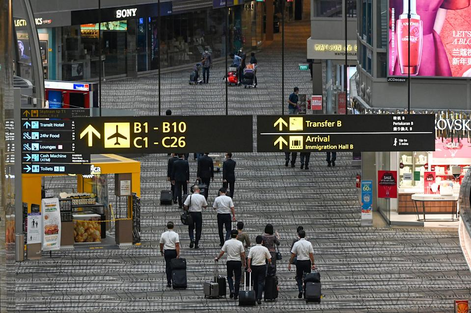 Singapore Airlines crew members and travellers walk along the transit hall of Changi International Airport terminal in Singapore on January 14, 2021. (PHOTO: AFP via Getty Images)