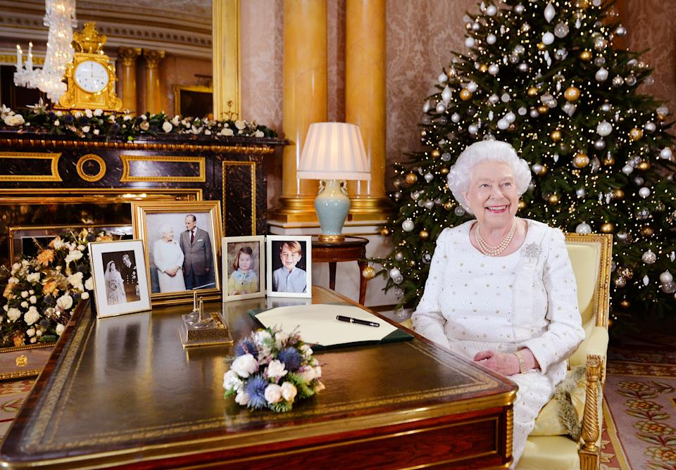 Britain's Queen Elizabeth is seen sitting at a desk in the 1844 Room after recording her Christmas Day broadcast to the Commonwealth, in Buckingham Palace, in this undated photograph received in London, Britain December 24, 2017. REUTERS/John Stillwell/Pool