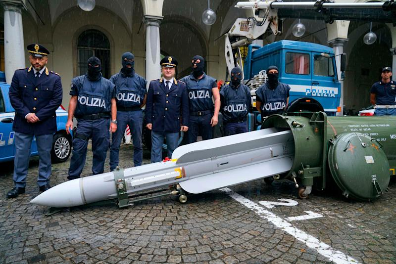 Police stand by a missile seized at an airport hangar near Pavia, northern Italy, following an investigation into Italians who took part in the Russian-backed insurgency in eastern Ukraine.