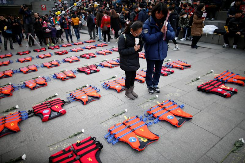 A mother prays with her daughter in front of life vests symbolising the 304 victims of sunken ferry Sewol during a protest demanding South Korean President Park Geun-hye's resignation in Seoul