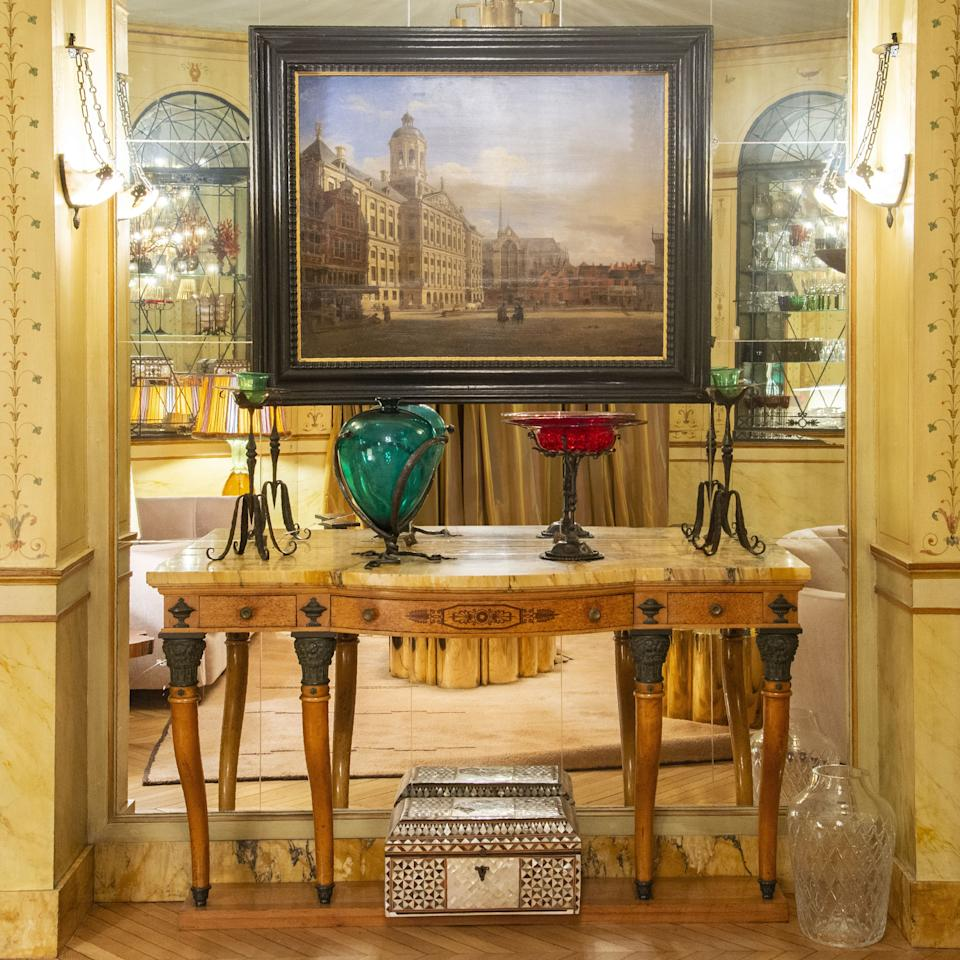 """<div class=""""caption""""> Also in the small salon, the alabaster wall sconces were created for the apartment circa 1930. The console is in the Empire style and the painting is by Dutch baroque painter Jan van der Heyden (1637–1712). On the floor is a 17th-century Turkish box with mother-of-pearl and tortoiseshell decoration. </div>"""