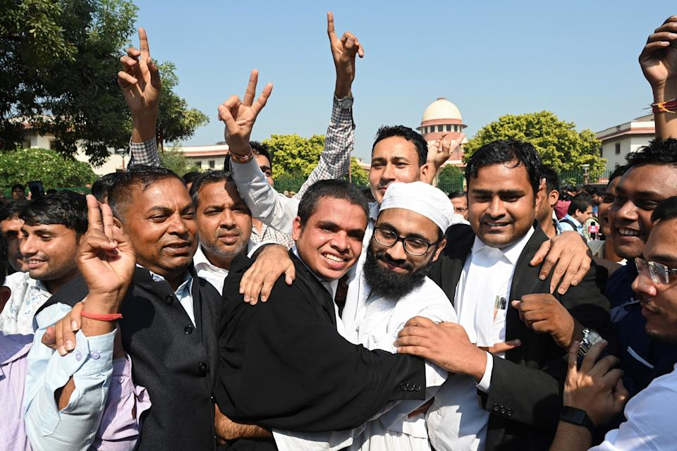 Lawyers and supporters hug a Muslim man at the Supreme Court in New Delhi on November 9, 2019, after a ruling over a holy site contested for centuries by Hindus and Muslims. - India's top court handed on November 9 a huge victory to Prime Minister Narendra Modi's Hindu nationalist ruling party by awarding Hindus control of a bitterly disputed holy site that has sparked deadly sectarian violence. (Photo by Money SHARMA / AFP) (Photo by MONEY SHARMA/AFP via Getty Images)