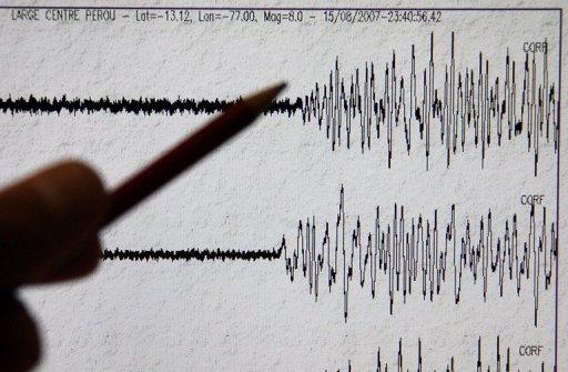 A scientist points to the seismograph of a major earthquake
