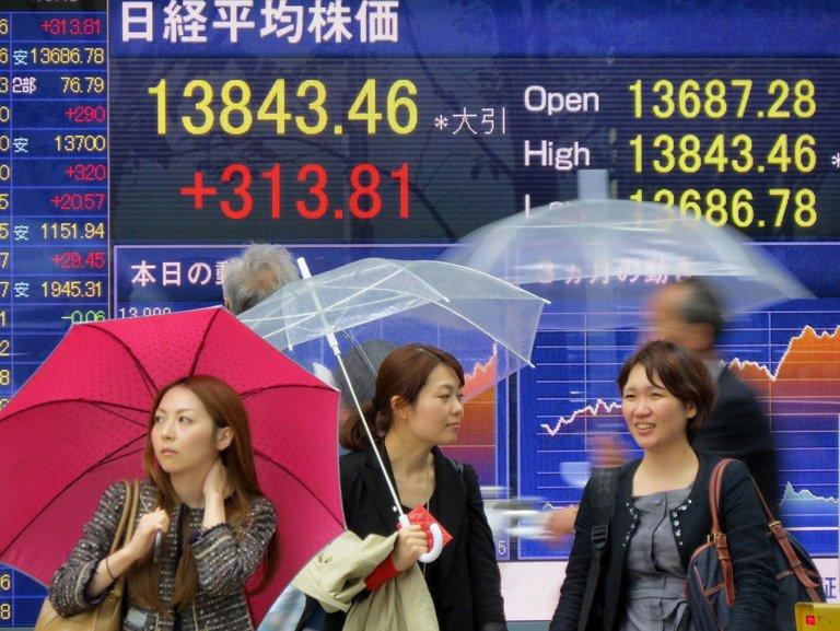 Pedestians stand in front of a share price board showing numbers at the Tokyo Stock Exchange in Tokyo on April 24, 2013