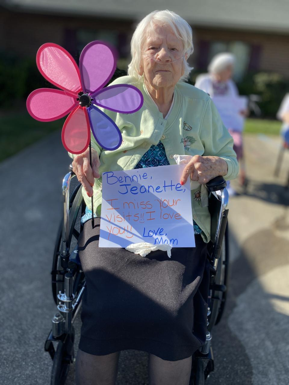 Daisy Swing holds a sign for her loved ones to see at Brookstone Retirement Center. (Photo: Jenny Brinkle)