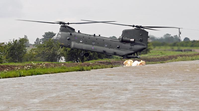 An RAF Chinook helicopter delivers personnel to the edge of the River Steeping (PA)