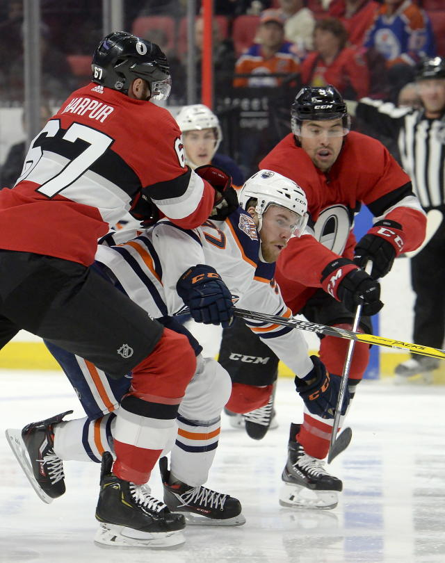 Edmonton Oilers' Connor McDavid (97) is tied up by Ottawa Senators' Ben Harpur (67) and teammate Cody Ceci during the first period of an NHL hockey game Thursday, Feb. 28, 2019, in Ottawa, Ontario. (Adrian Wyld/The Canadian Press via AP)