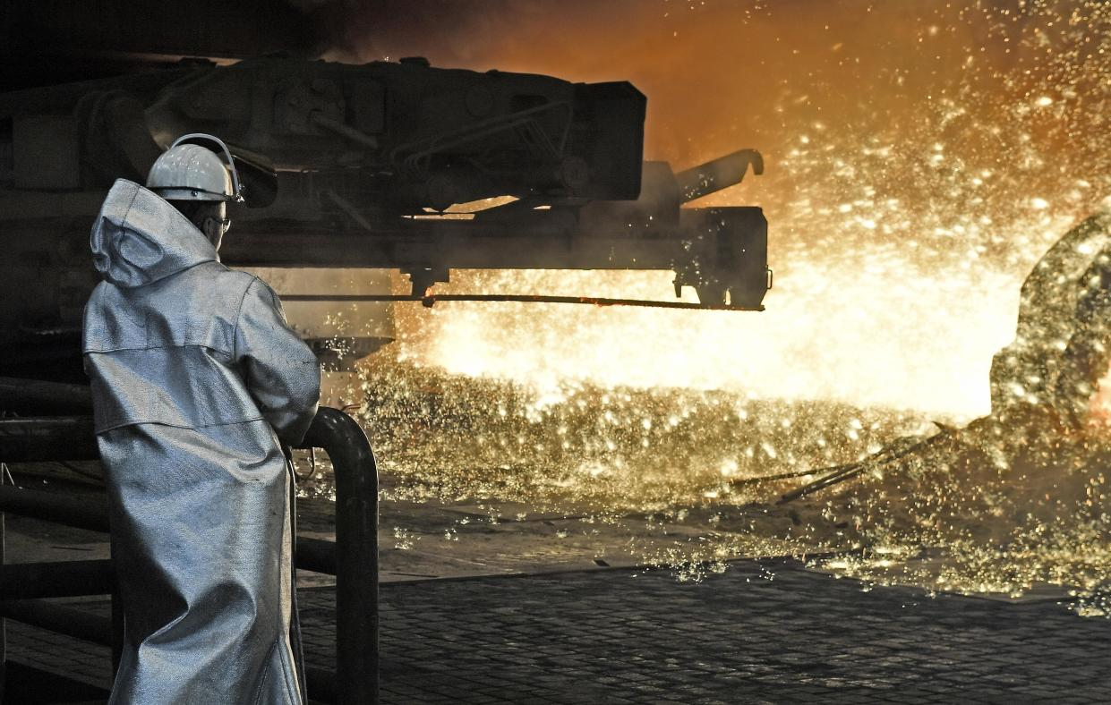 A steel worker watches the hot metal at the Thyssenkrupp steel factory in Duisburg, Germany, Friday, April 27, 2018. Duisburg is the biggest steel producer site in Europe. (AP Photo/Martin Meissner)