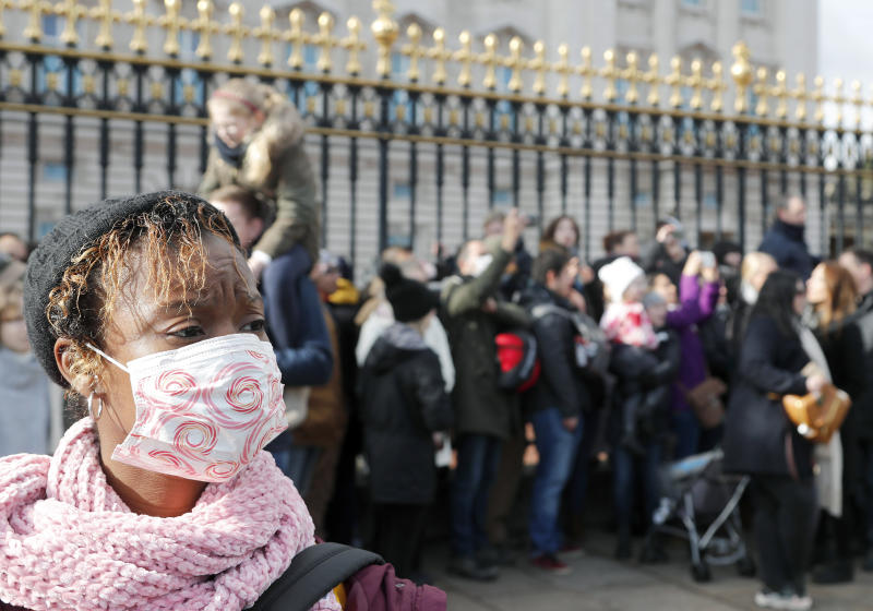 """A tourist wears a face mask as she watches the Changing of the Guard, at Buckingham Palace, in London, Monday, March 2, 2020. British Prime Minister Boris Johnson told reporters Sunday at a health center in London that he was """"very, very confident"""" that Britain's National Health Service can cope with the coronavirus outbreak. (AP Photo/Frank Augstein)"""
