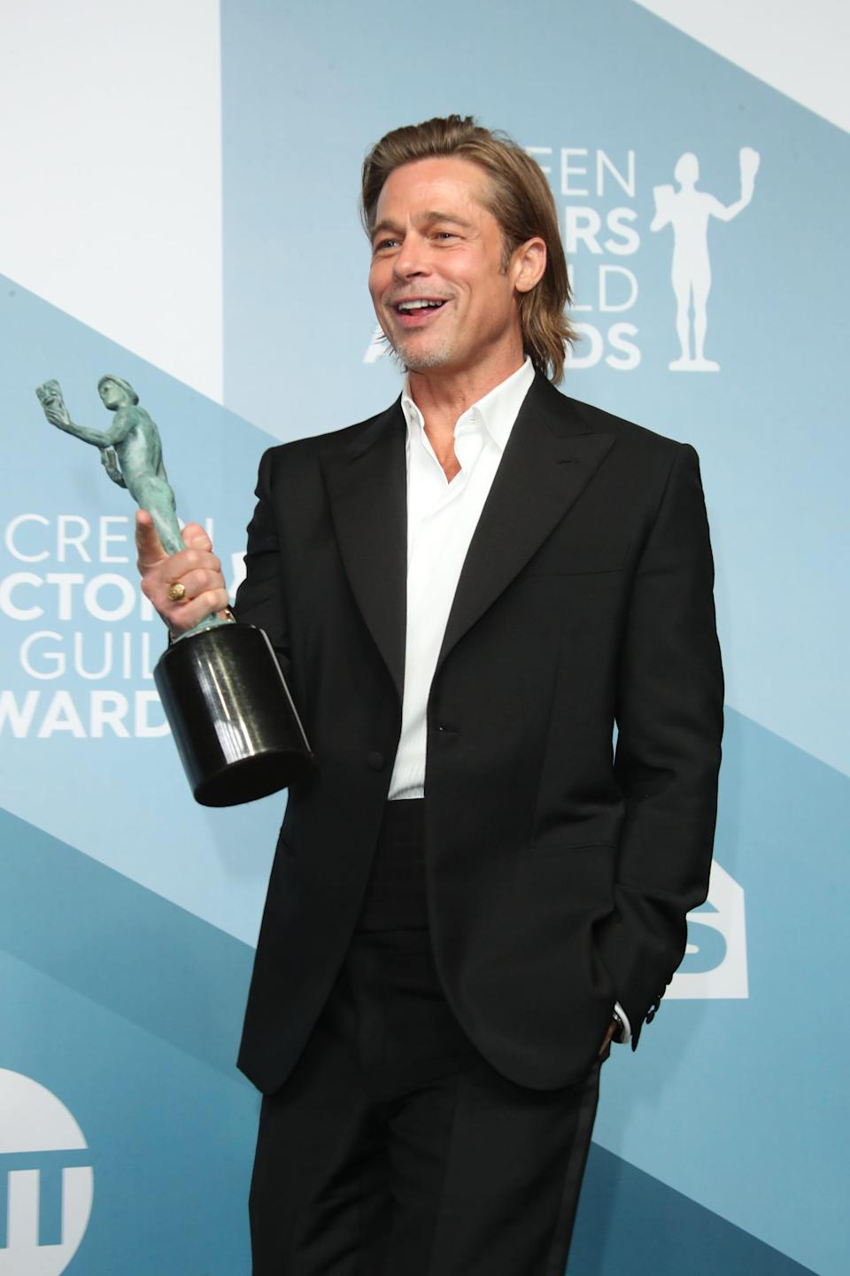 """In the press room, Brad Pitt shows off his SAG award for outstanding performance by a male actor in a supporting role for """"Once Upon a Time in Hollywood."""""""