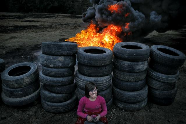 In this photo taken on Sunday, March 10, 2019, a little girl rests leaning against used tires during a ritual marking the upcoming Clean Monday, the beginning of the Great Lent, 40 days ahead of Orthodox Easter, on the hills surrounding the village of Poplaca, in central Romania's Transylvania region. Romanian villagers burn piles of used tires then spin them in the Transylvanian hills in a ritual they believe will ward off evil spirits as they begin a period of 40 days of abstention, when Orthodox Christians cut out meat, fish, eggs, and dairy. (AP Photo/Vadim Ghirda)
