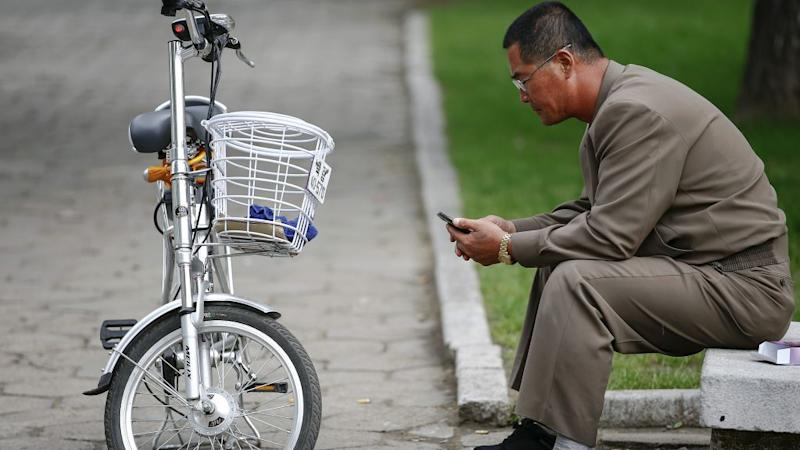 A man uses his mobile phone next to an electric bicycle in downtown Pyongyang.