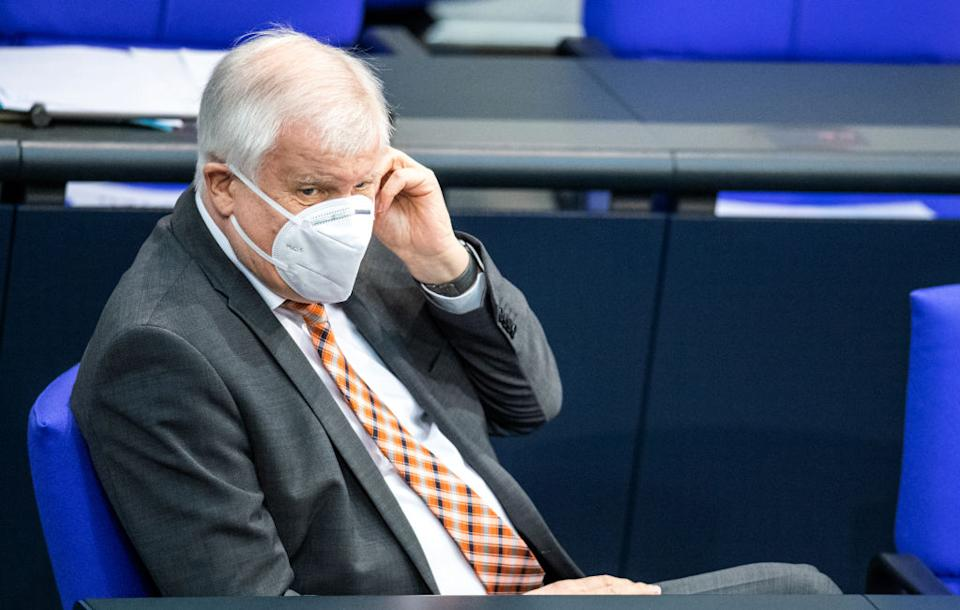 28 January 2021, Berlin: Horst Seehofer (CSU), Federal Minister of the Interior, for Construction and Home Affairs, directs his mouth-nose-covering during the plenary session in the German Bundestag. The main topics of the 206th session of the 19th legislative period are the annual economic report, a bill to increase IT security for critical infrastructure, the ordinance on the listing of election candidates under Corona conditions and the draft law on the mobilization of building land. Photo: Dorothée Barth/dpa (Photo by Dorothée Barth/picture alliance via Getty Images)
