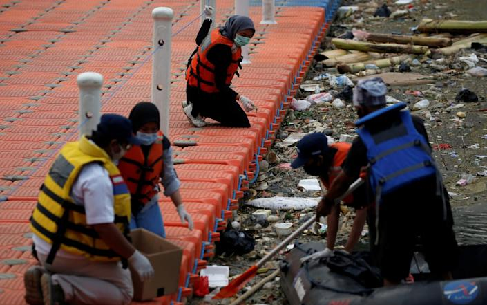 Volunteers work in teams to pull waste out of the river - REUTERS