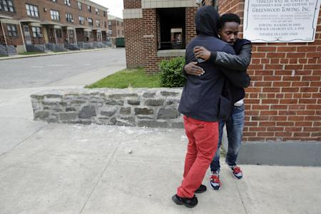 Ronte Jenkins, right, a lifelong friend of Freddie Gray, hugs a friend at the site of Gray's arrest, back left, Friday, May 1, 2015, in Baltimore, after the announcement of charges against the police officers involved in Gray's arrest. (AP Photo/Patrick Semansky)