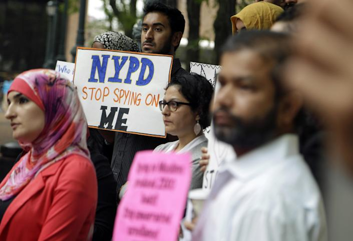 FILE - In this Aug. 28, 2014, file photo, a group of people hold signs protesting the New York Police Department's program of infiltrating and informing on Muslim communities during a rally near police headquarters in New York. On Tuesday, April 15, 2014, the NYPD confirmed it disbanded the special intelligence unit that monitored Muslim communities in New York and New Jersey. (AP Photo/Seth Wenig, File)