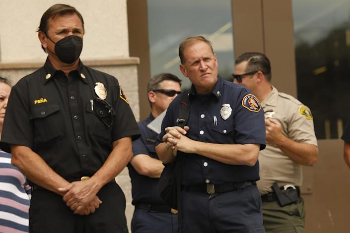 Two uniformed firefighters, one wearing a face mask, stare intently.