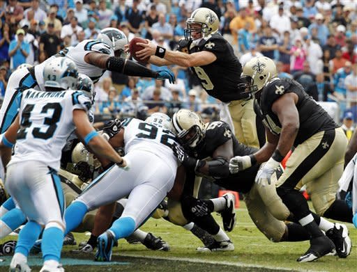 New Orleans Saints' Drew Brees (9) reaches the ball over the goal line for a touchdown against the Carolina Panthers during the fourth quarter of an NFL football game in Charlotte, N.C., Sunday, Sept. 16, 2012. The Panthers won 35-27. (AP Photo/Bob Leverone)