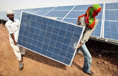 FILE PHOTO: Workers carry a damaged photovoltaic solar panel at the Gujarat solar park under construction in Charanka village in Patan district of the western Indian state of Gujarat, April 14, 2012. REUTERS/Amit Dave/File Photo