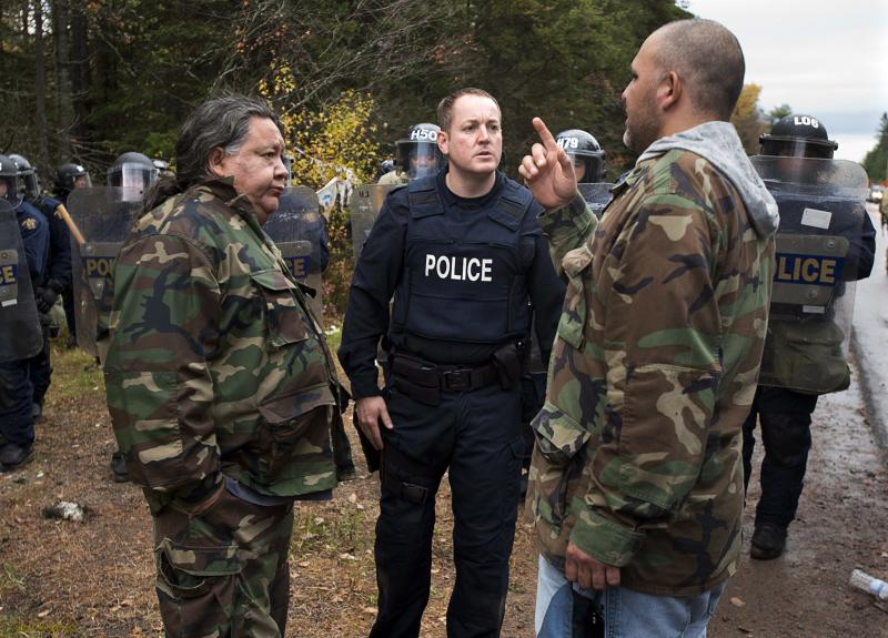 In this Oct. 17, 2013 photo, protesters negotiate with a police officer in Rexton, New Brunswick as police began enforcing an injunction to end an ongoing demonstration against shale gas exploration in eastern New Brunswick. Canada is facing a crisis over aboriginal issues despite years of efforts to overcome tensions and address social problems, a U.N. expert who recently visited the country said Monday, Oct. 21, 2013. (AP Photo/The Canadian Press, Andrew Vaughan)
