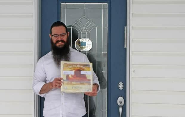 Rabbi Raphael Kats stands outside his home in Saskatoon  with a box of matzah, which is unleavened bread traditionally had during Passover in April 2020.