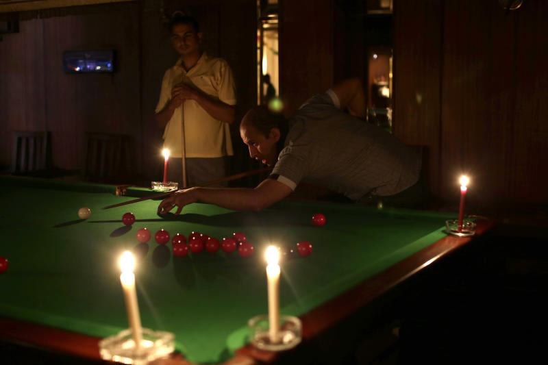 Egyptian men play snooker by candlelight at a club in the Mohandessin district, in Giza, Egypt, Saturday, May 25, 2013.  Blackouts happened under autocratic leader Hosni Mubarak, ousted in a 2011 uprising, and became more noticeable last summer. In recent months, as temperatures climb again, they have become part of Egyptians' daily routine, even in the most upscale districts of the capital. Along with a stuttering economy, traffic-clogging street protests, and a crime wave, they have come to symbolize the disorder of the post-Mubarak era. The government has urged citizens to cut down use of electricity during the summer and said it is working on securing enough funds to buy fuel to solve the problem.(AP Photo/Hassan Ammar)