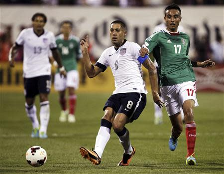 United States' Clint Dempsey (8) passes the ball under pressure from Mexico's Jesus Zavala (17) during the first half of their 2014 World Cup qualifying soccer match in Columbus, Ohio September 10, 2013. REUTERS/Matt Sullivan