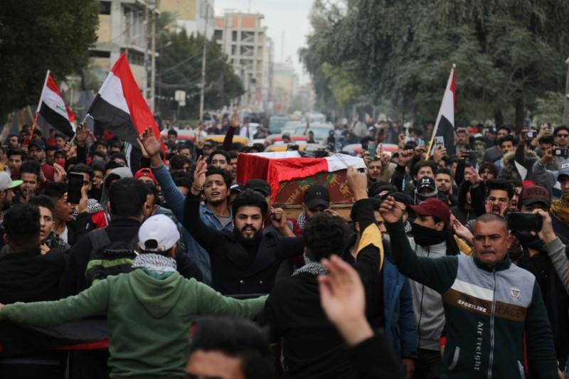 Mourners carry a coffin of an Iraqi demonstrator, who was killed last night at the ongoing anti-government protests during the funeral in Kerbala