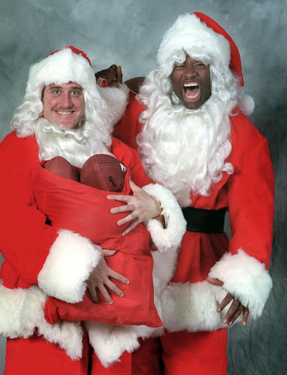 """In 1996, linebackers Kevin Greene (left) and Lamar Lathon dressed up as Santa Claus for a Charlotte Observer photo. Greene and Lathon were nicknamed """"Salt and Pepper."""" In that season and combined for 28 sacks, the most by a pass-rushing duo in Carolina history."""