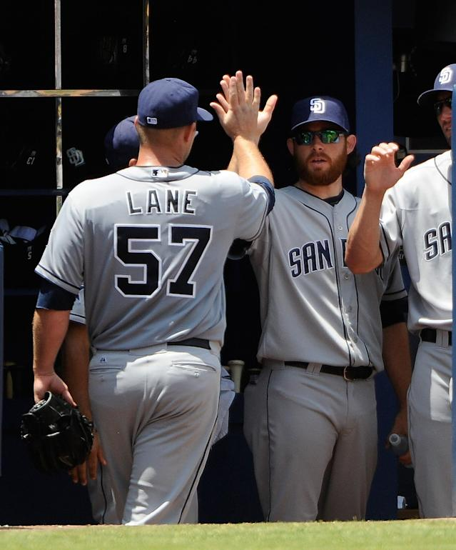 San Diego Padres' Jason Lane (57) is congratulated by teammates after he leaves his first game as a starting pitcher during the seventh inning of a baseball game against the Atlanta Braves Monday, July 28, 2014, in Atlanta. (AP Photo/David Tulis)