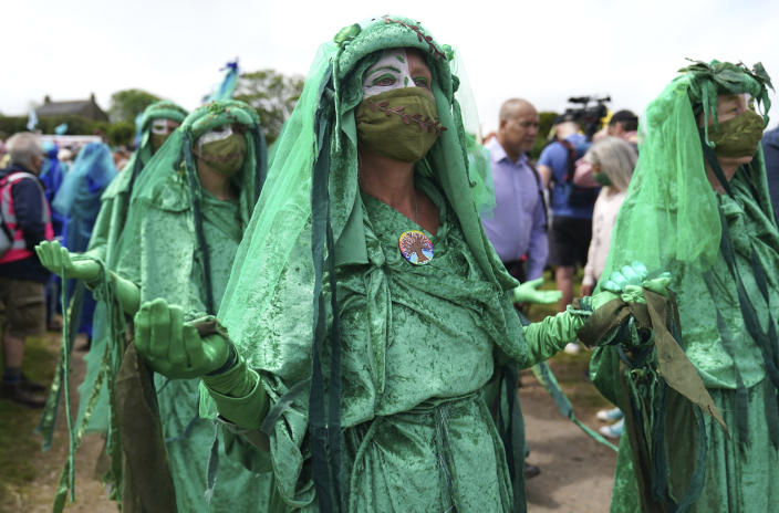 Climate activists are dressed in costumes as they demonstrate near the G7 meeting taking place in St. Ives, Cornwall, England, Friday, June 11, 2021. Leaders of the G7 begin their first of three days of meetings on Friday in Carbis Bay, in which they will discuss COVID-19, climate, foreign policy and the economy. (AP Photo/Jon Super)