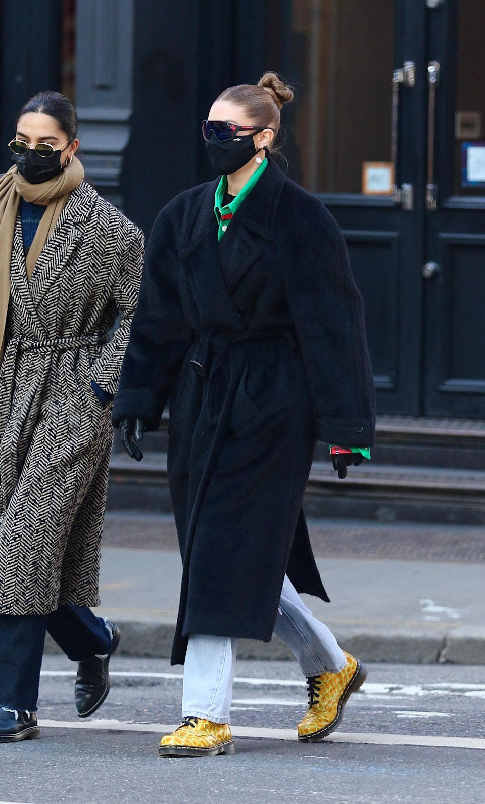 Since giving birth, Gigi has been hitting the streets of Manhattan with some of her cozier winter looks ever. This day, she opted for a pair of light-wash jeans and a black maxi coat. To add a pop of color, she went for some funky Dr. Martens (a winter must-have) and a forest green shirt. The star of the show, though? Her Prada shield sunglasses.