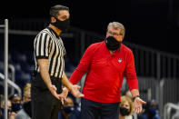 Connecticut head coach Geno Auriemma, right, questions an official after one of his players received a technical foul during the third quarter of an NCAA college basketball game against Butler in Indianapolis, Saturday, Feb. 27, 2021. (AP Photo/Michael Conroy)