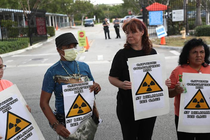 Odalys K. Fernandez, Laurie Woodward Garcia and Yaquelin Lopez protest outside an ICE office in Miramar, Fla.